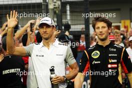 (L to R): Jenson Button (GBR) McLaren and Romain Grosjean (FRA) Lotus F1 Team on the drivers parade. 21.09.2014. Formula 1 World Championship, Rd 14, Singapore Grand Prix, Singapore, Singapore, Race Day.