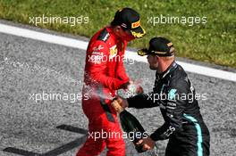 (L to R): Charles Leclerc (MON) Ferrari and race winner Valtteri Bottas (FIN) Mercedes AMG F1 celebrate on the podium. 05.07.2020. Formula 1 World Championship, Rd 1, Austrian Grand Prix, Spielberg, Austria, Race Day.
